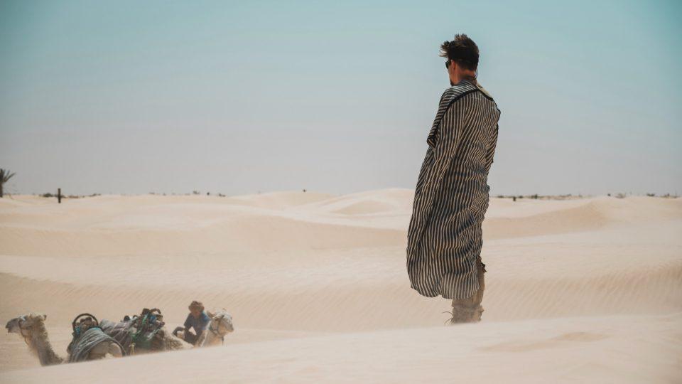 Tomáš v poušti v tradičním oblečení.