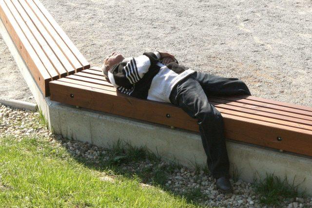 Bezdomovec spí na lavičce